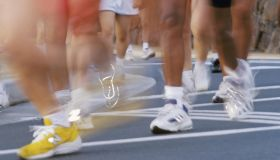 Blurred action image of runners feet during race, reflective shoes