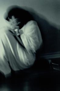 Woman curled on floor shielding herself with hands, blurred (B&W)