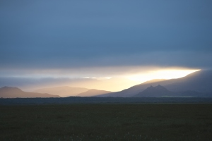 Sunlight coming through the clouds over a landscape of mountains and fields, Iceland.
