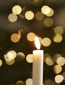 single candle with christmas lights in background