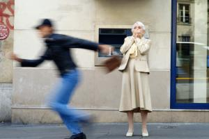 Thief stealing elderly woman's handbag
