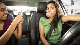 Teenage girls clown around in car