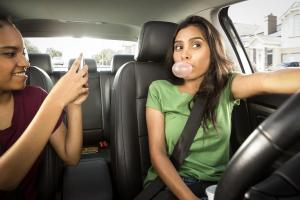 Teenage girls clown around in car