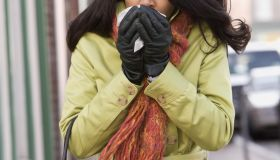 Woman sneezing on sidewalk