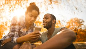 Young African American couple using smart phone during autumn day in nature.