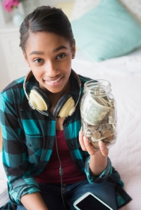 Mixed Race girl holding jar containing cash and coins