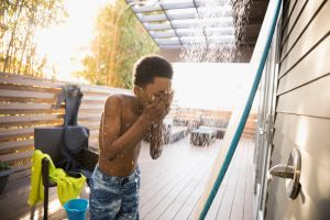 African American boy in swim trunks using beach house shower on deck