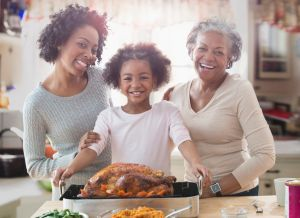 Three generations of women cooking together in kitchen