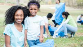 Mother volunteers with young daughter for community cleanup