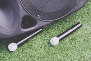 High Angle View Of Microphones And Speaker On Grassy Field
