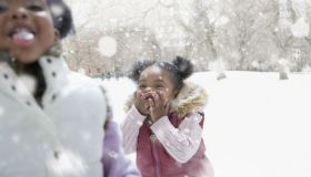 Mixed race girl playing outdoors in falling snow