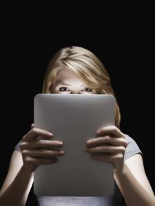 Girl holding glowing digital tablet