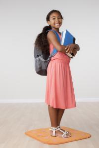 Studio portrait of girl (8-9) carrying backpack