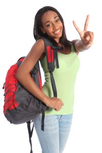 V for victory success by pretty young African American teenager school girl, with long black hair wearing green t-shirt and red school backpack with beautiful smile.