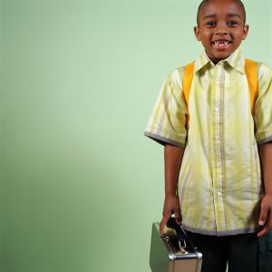 Boy (5-7) wearing backpack, carrying lunchbox, portrait