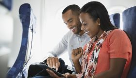 Couple using digital tablet in airplane