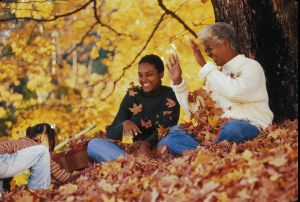 Three generation family playing with autumn leaves