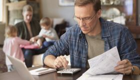 Father paying bills with family behind him