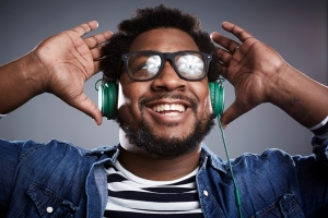 Studio portrait of mid adult man listening to headphones